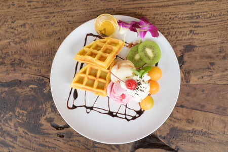 waffles  ice-cream with melon and kiwi decorated by orchid and mint