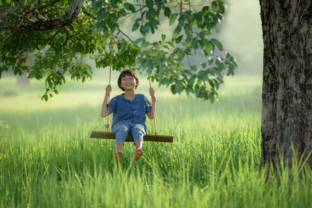 beautiful Asian girl plays swing under big tree with green field background Stok Fotoğraf - 64620099