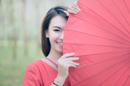 portrait of beautiful girl in red dress smiling with red umbrella Stok Fotoğraf