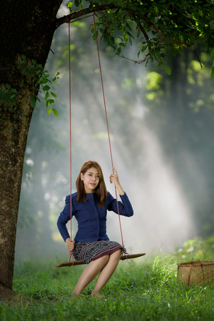 beautiful Asian girl plays swing under big tree with green field background