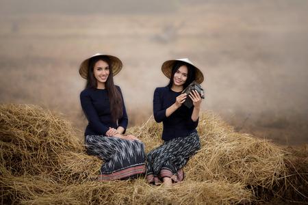 beautiful farmer girls are listening radio on a lot of straw in farm