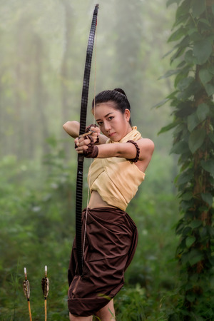 Beautiful ancient archery woman with bow and arrows aiming in forest background Banco de Imagens