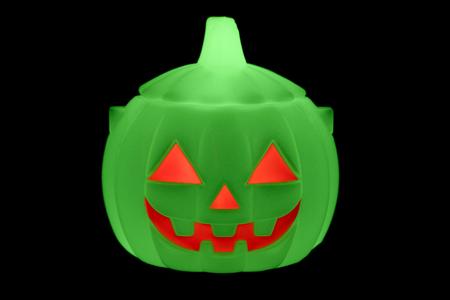 green fluorescent halloween pumpkin isolated on black