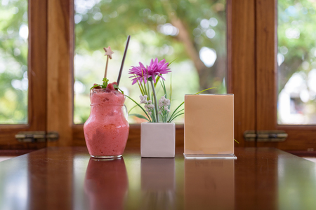 Strawberry smoothie in jar and menu on window with nature background, healthy food