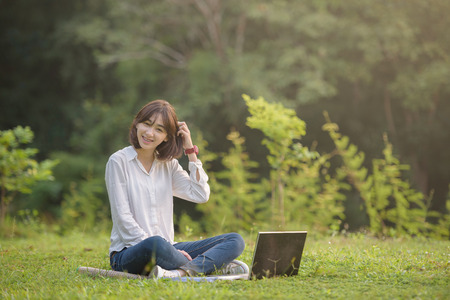 beautiful female student with laptop working outdoor with beautiful light and nature background