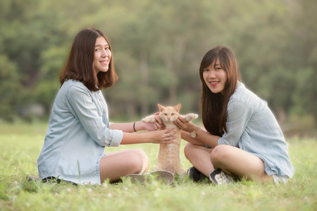 smiling beautiful young women sitting and playing with domestic cat outdoor happily Stok Fotoğraf - 69523073