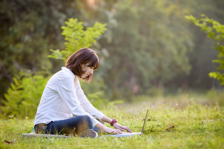 beautiful caucasian college student with laptop working outdoor with beautiful light and nature background, beautiful caucasian texting on laptop Stok Fotoğraf - 71441855