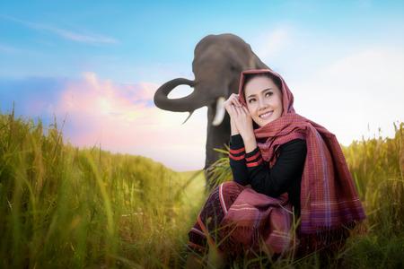 beautiful girl and elephant, elephant village, Surin, Thailand, woman harvest rice with elephant in surin Thailand, beautiful woman in farmland, woman in rice field Thailand, woman and elephant harvest in rice field with beautiful sky in Thailand