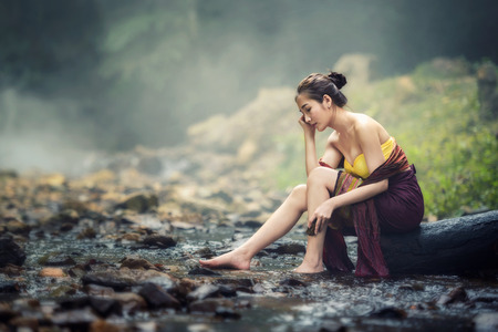 portrait of beautiful Asian woman in traditional costume sitting on stump in creek Stock Photo