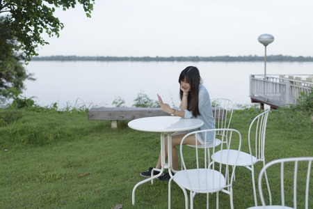 Portrait of young woman use mobile phone while sitting outdoor, smiling happy female reading on cell telephone, woman typing text message on smart phone in outdoor cafe, image of young woman sitting at a table using mobile phone. Stok Fotoğraf - 71409412