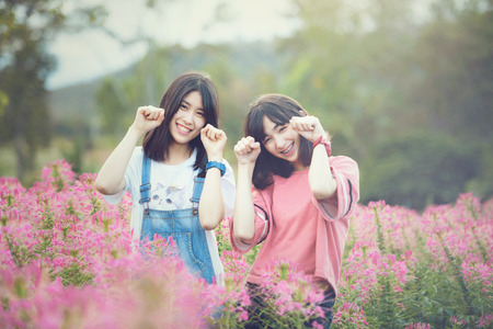 Beautiful Caucasian girls smiling with happiness in cosmos flower field Stok Fotoğraf