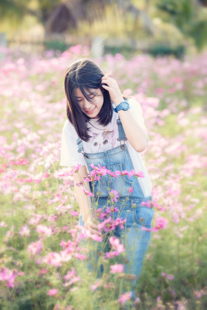 Beautiful Asian girl is smiling in pink cosmos flower field Stok Fotoğraf