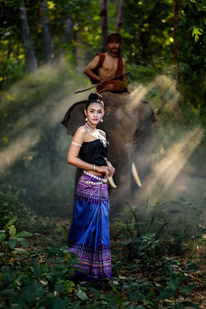 portrait of beautiful Asian woman in traditional dress with elephant and mahout background Stok Fotoğraf - 72751847