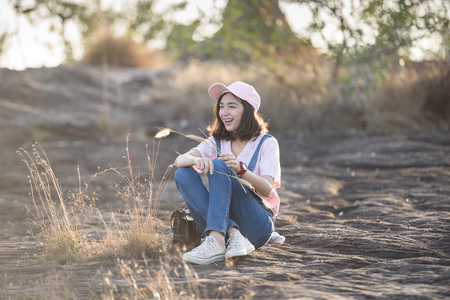 beautiful caucasian girl holding grass flower in hand smiling with beautiful light Stok Fotoğraf - 71409422