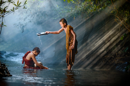 novice monk Thailand are bathing in creek happily with stunning sunlight background Stok Fotoğraf - 72751848