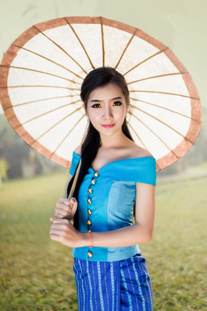 beautiful Asian women (Laos)  in sky blue traditional costume hlding umbrella Stok Fotoğraf