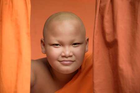head shot of smiling Buddhist novice monk with yellow robe background Stok Fotoğraf - 71390287