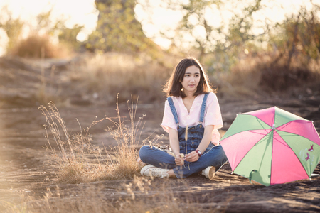 beautiful caucasian girl holding grass flower in hand smiling with beautiful light Stok Fotoğraf - 71390524