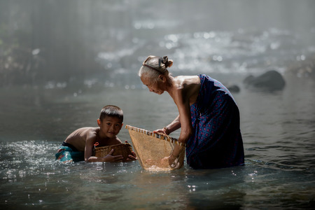 grandmother and nephew fishing in creek happily, countryside life style,