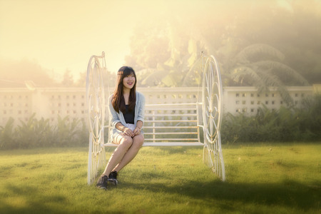 portrait of smiling beautiful Asian woman sitting alone on white bench during sun set with blurry background