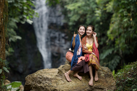 portrait of beautiful Asian woman in traditional costume with water fall background