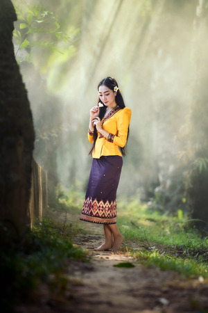beautiful Asian women (Laos)  in yellow purple traditional costume with stunning light background
