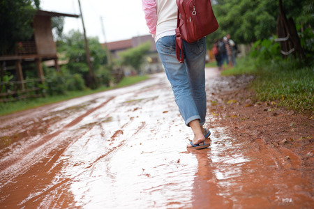 woman is walking on wet dirt road  in countryside after raining Stok Fotoğraf