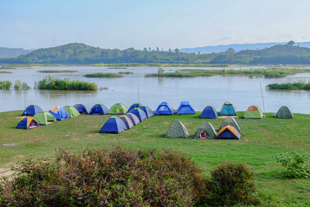 camping and tents nearby river in morning
