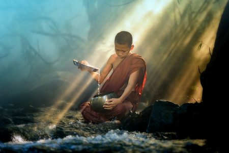novice monk washes alms bowl in creek with stunning rays of sunlight