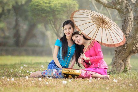 beautiful Asian women (Laos)  in pink and sky blue traditional suit is sitting and smiling happily under Plumeria tree with flower fallen on floor