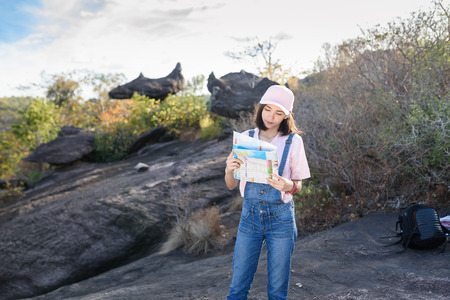 beautiful caucasian backpacker holding map in hand finding somewhere with nature background