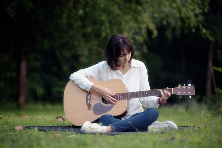 beautiful girl playing guitar in park, classic guitar, wooden guitar, chord guitar, solo guitar, acoustic guitar Stok Fotoğraf - 71390823