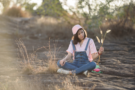 beautiful caucasian girl holding grass flower in hand smiling with beautiful light
