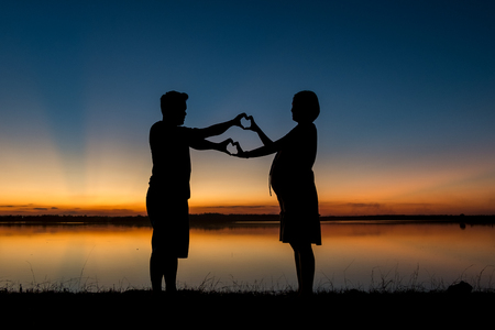 silhouette of dad and pregnancy mom at sunset with beautiful nature background Stok Fotoğraf