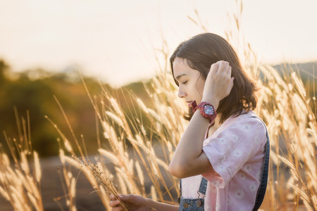 beautiful caucasian girl holding grass flower in hand smiling with beautiful light during sunset Stok Fotoğraf