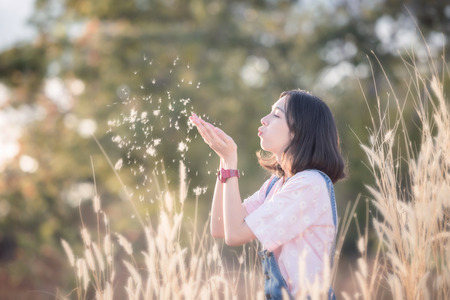 girl looking up: beautiful caucasian girl blowing grass flower Stock Photo