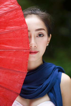 portrait of beautiful Asian woman in traditional costume with red umbrella cover a half of her face, woman with beautiful eyes smiling behide red umbrella Stok Fotoğraf