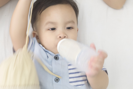 sleepy cute boy holding and sucking bottle of milk Stok Fotoğraf - 123892517