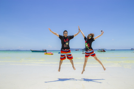 smiling couples are jumping high in beach with blue sky and sea background Stok Fotoğraf