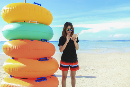 beautiful girl who wearing sun glasses is using smartphoone on beach nearby colorful swim rings with blue sea and blue sky background Stok Fotoğraf