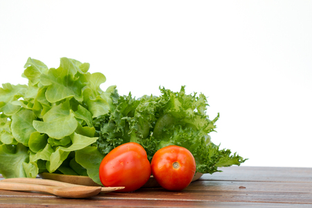 Set of salad which are tomato, Frilly Iceberg and green oak on wooden tray with spoon and fork Stock Photo