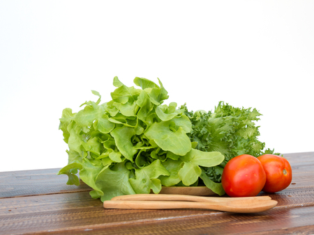 salad set are tomato, Frilly Iceberg and green oak placing on wooden tray with spoon and fork on white background Stock Photo