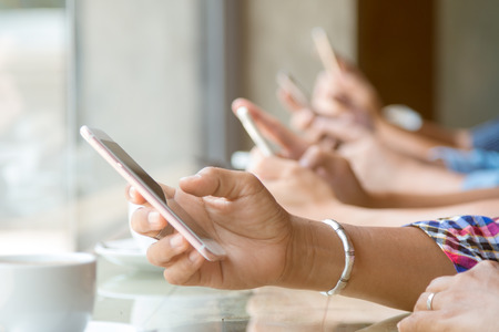Close up of four people hand holding mobile phone and using internet in coffee shop with warm light flare