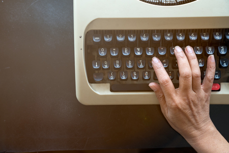Close up of Senior secretarial typing the memo by old typewriter which placing on the rusty table