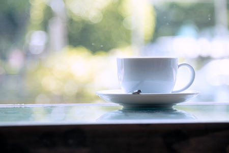 White Coffee Cup placing on table near window with bokeh from outside