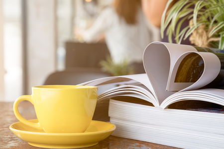 Close up of yellow coffee cup placing together with magazine like Heart Shape Stock Photo