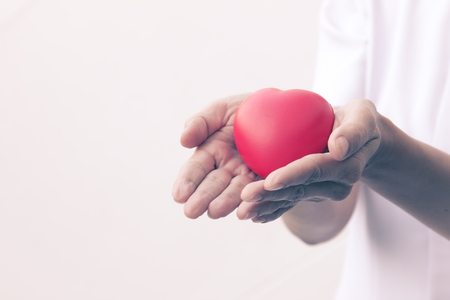 Close up of Asian Nurse holding red heart in hands; health-care concept; love heart for valentine Stock Photo