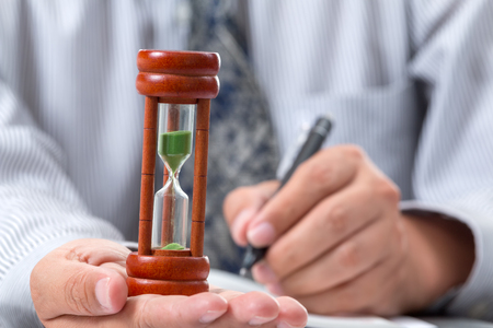 Close up sandglass laying on right hand of businessman taking note Banque d'images - 94490646