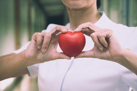Infermiera femminile senior che tiene cuore rosso con amore per il San Valentino Archivio Fotografico - 94490647