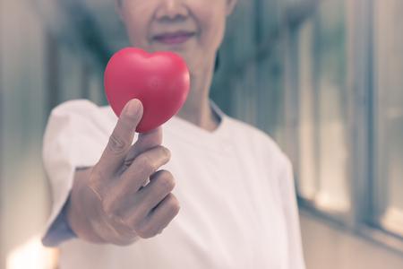 Infermiera femminile senior che tiene cuore rosso con amore per il San Valentino Archivio Fotografico - 94490648